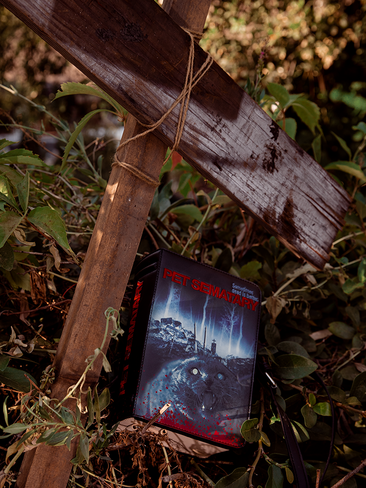 Pet Sematary Book Purse along with a makeshift cross made with discarded and mismatched wood.