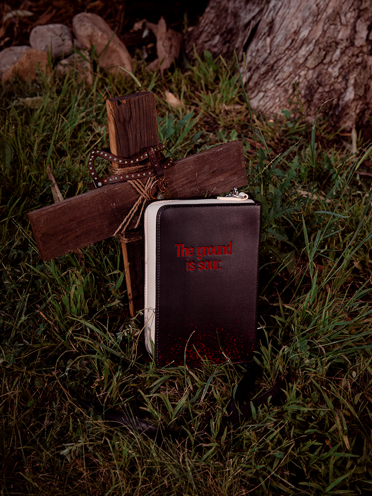 Back image of the Pet Sematary book purse resting in a grassy area next to a woodenc ross with an animal collar draped across the top.