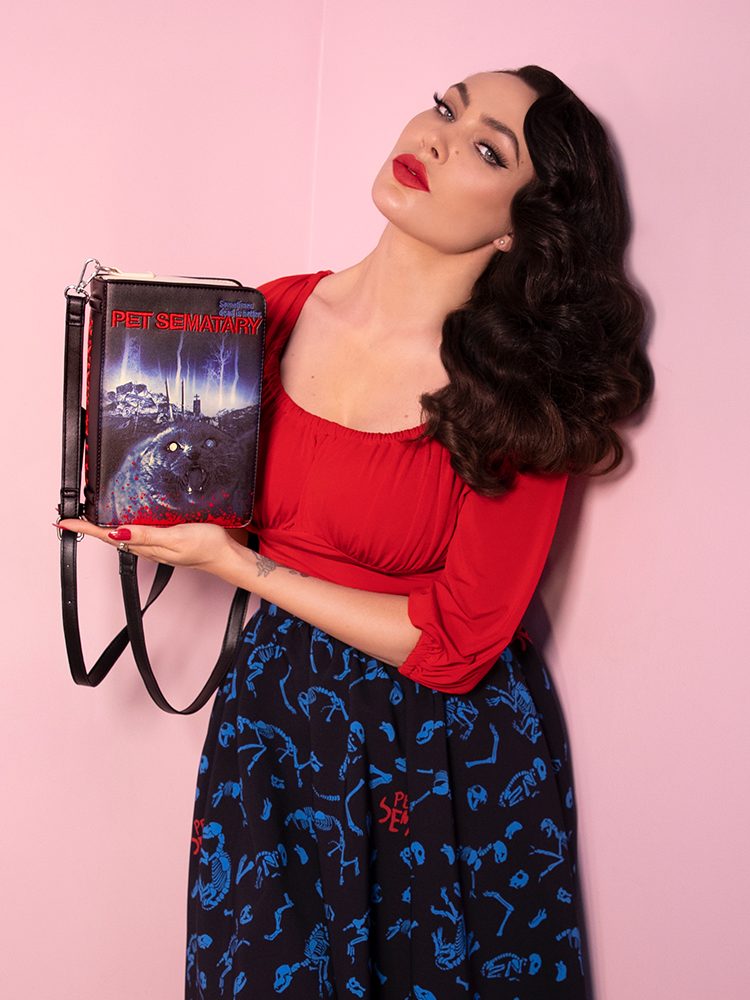 Micheline Pitt posing with the Pet Sematary book purse.