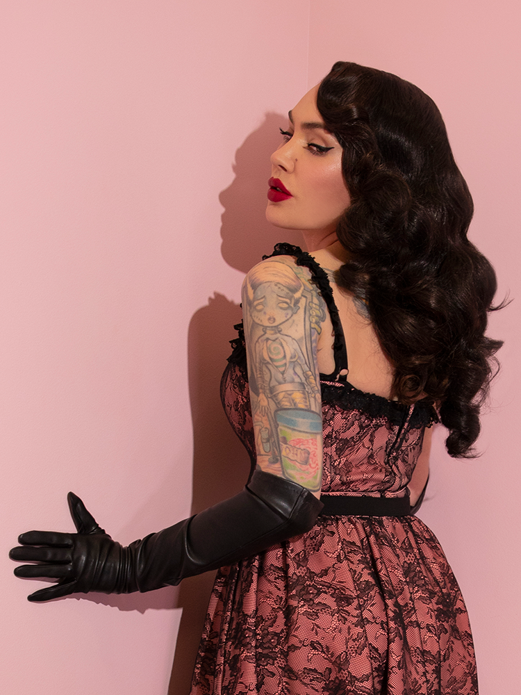 Micheline Pitt turned away from the camera while modeling the Vixen Bustier Crop Top in Peach and Black Lace.