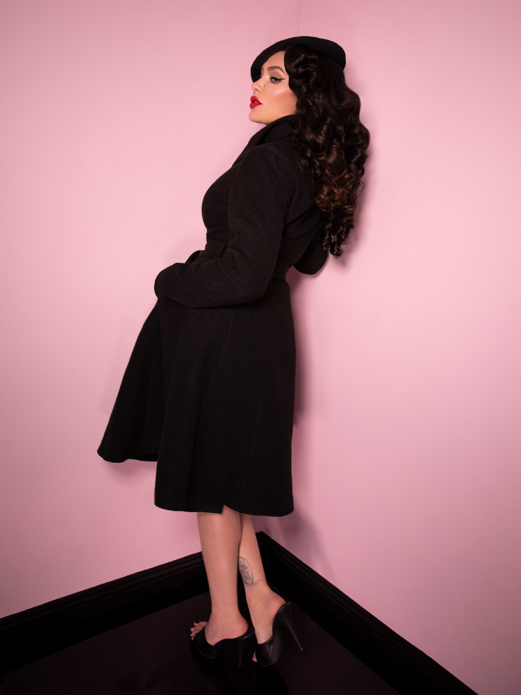 Side view of Micheline Pitt buttoned up in the Starlet Swing Coat in Black.