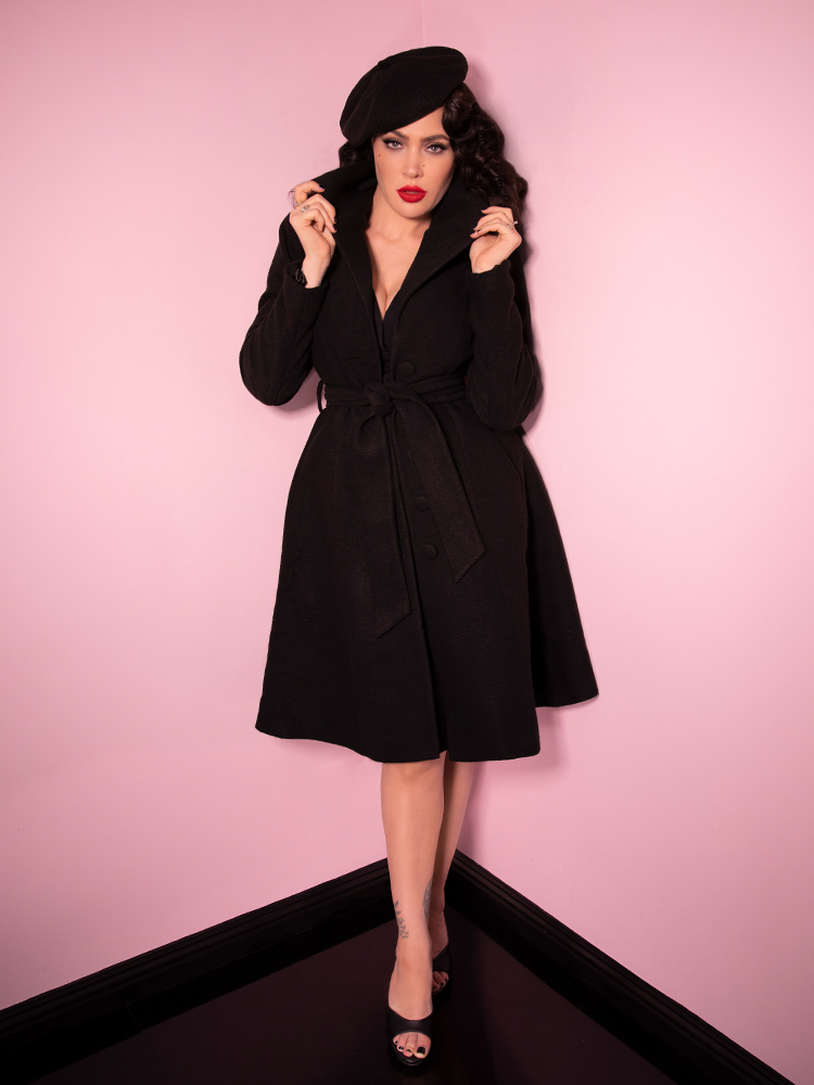 Flipping the collar up on the Starlet Swing Coat in Black, Micheline Pitt stuns in a vintage style outfit.
