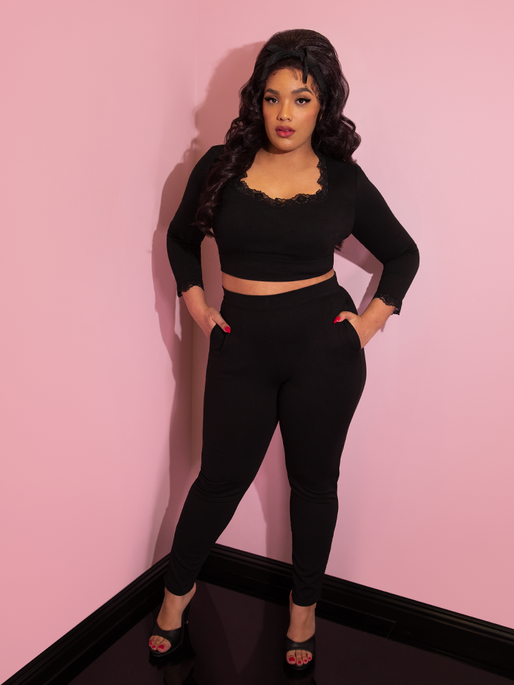 Ashleeta with her hands in her pockets modeling the Vixen Clothing black ponte cigarette pants paired with a matching crop top.