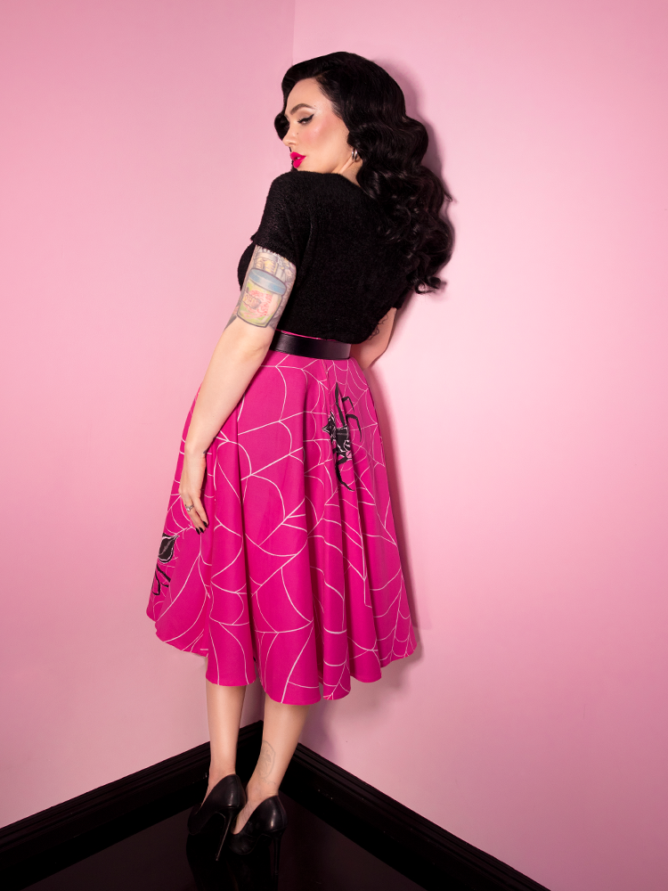 Turned away from the camera but subtly looking back at it, Micheline Pitt wears the Circle Skirt in Pinky Spider Print.