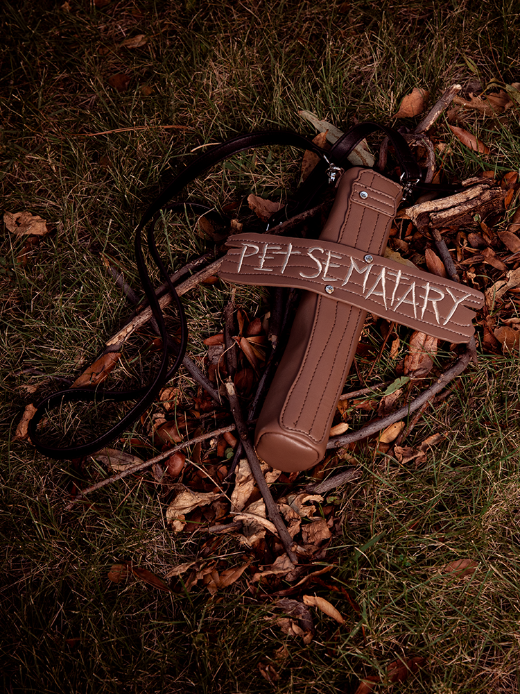Shot on the ground amongst grass, sticks and leaves the Pet Sematary purse from Vixen Clothing is featured.