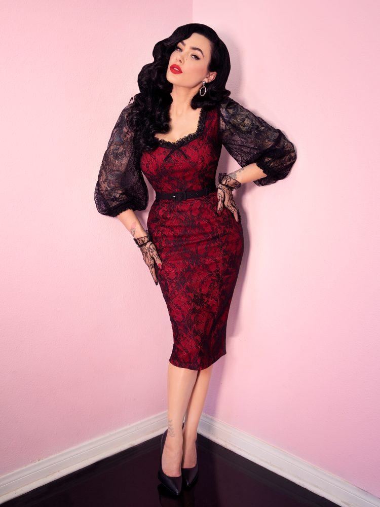 Micheline Pitt, posing while standing up with her hands placed on her hips, modeling the retro dress entitled the Decadence Wiggle Dress in Red from Vixen clothing.