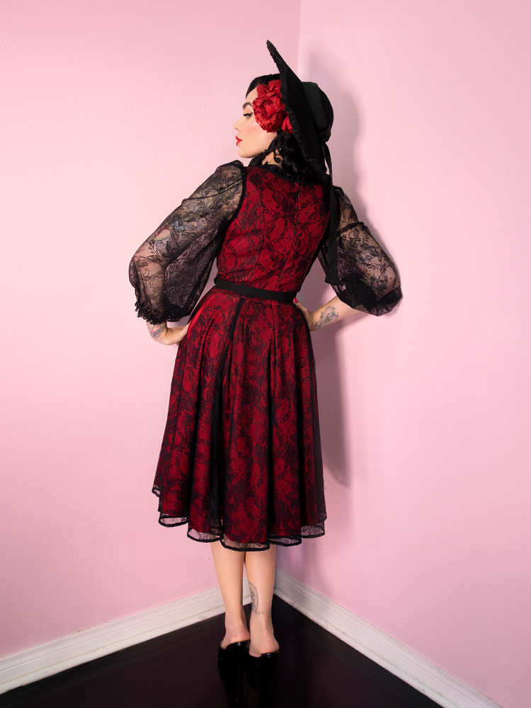 Back shot of model wearing red and black lace dress with matching black hat and faux red rose headpiece.