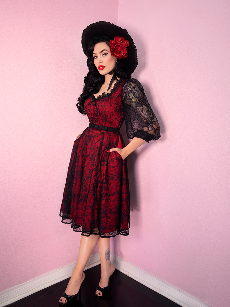 Wide out shot of Micheline Pitt wearing a retro inspired red dress with matching hat and floral piece.
