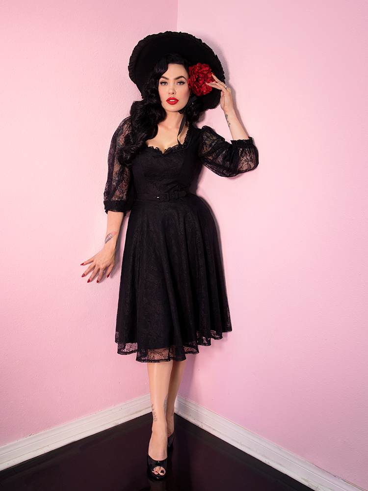 Full body picture of Micheline Pitt wearing a retro inspired dress entitled the Decadence Swing Dress in Black from Vixen Clothing.