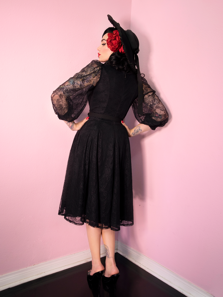 With her body facing the pink walls and head turned slightly while peering back at the camera, Micheline Pitt models a black dress made featuring lace accents and sleeves.