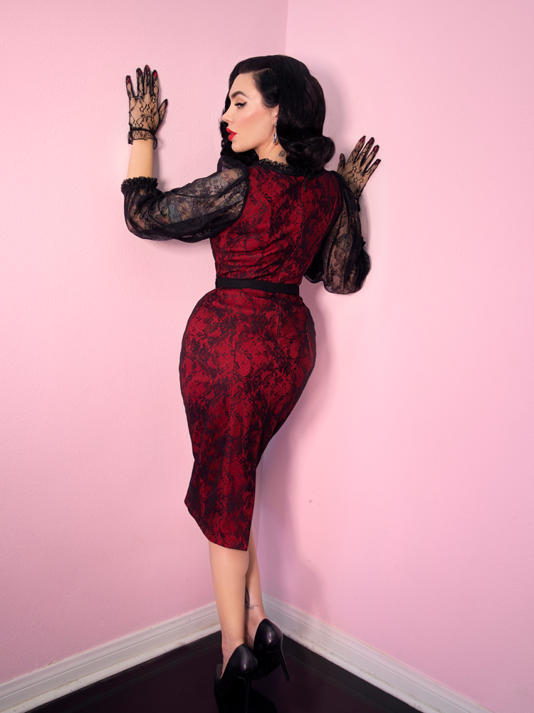 Micheline Pitt, facing the pink walls in her studio with her hands placed on either side of intersecting walls, models the vintage inspired Decadence Wiggle Dress in Red.