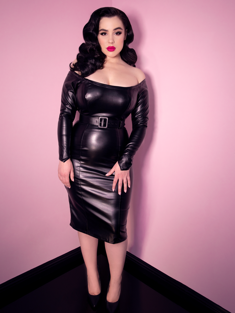 Standing and with her hands place gently on her upper legs, an attractive black-haired model shows off the latest retro dress from Vixen Clothing.