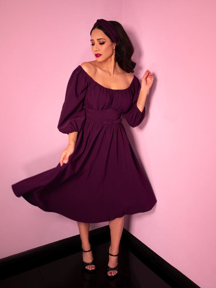 Full length photograph of Milynn Moon spinning in the Vacation Dress in Eggplant from retro dress retailer Vixen Clothing.