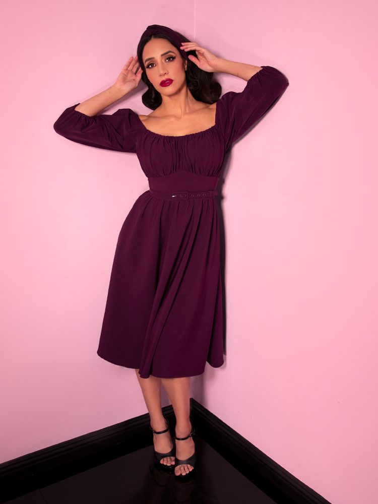 Adjusting her matching headband, Milynn Moon models the new eggplant colored vintage inspired Vacation Dress from Vixen Clothing.