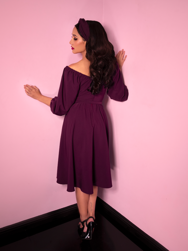 Milynn Moon facing away from the camera with her head tilted back slightly while wearing the Vacation Dress in Eggplant from Vixen Clothing.