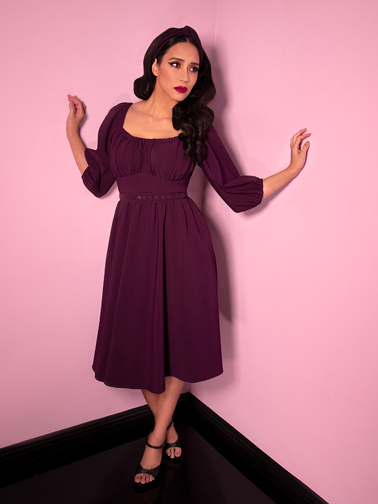 Milynn Moon looking offcamera while posing in the corner of a room with her hands touching the walls on either side of her while wearing the Vacation Dress in Eggplant from Vixen Clothing.