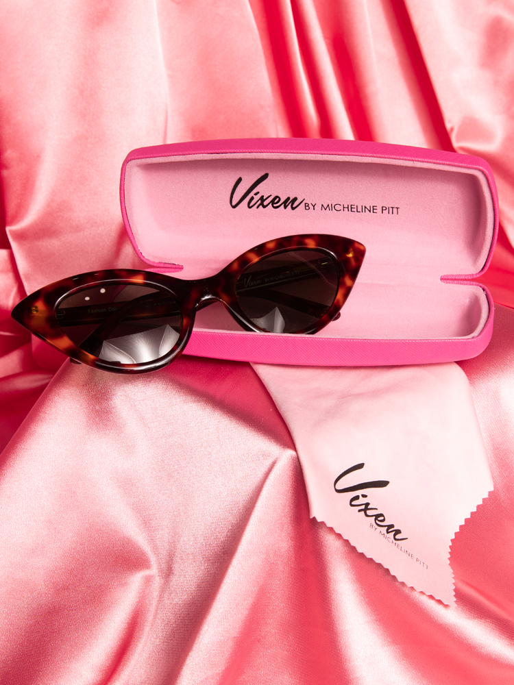 Stylized shot of the Fashion Doll Cat Eye Sunglasses in tortoise shell placed on a pink satin background.
