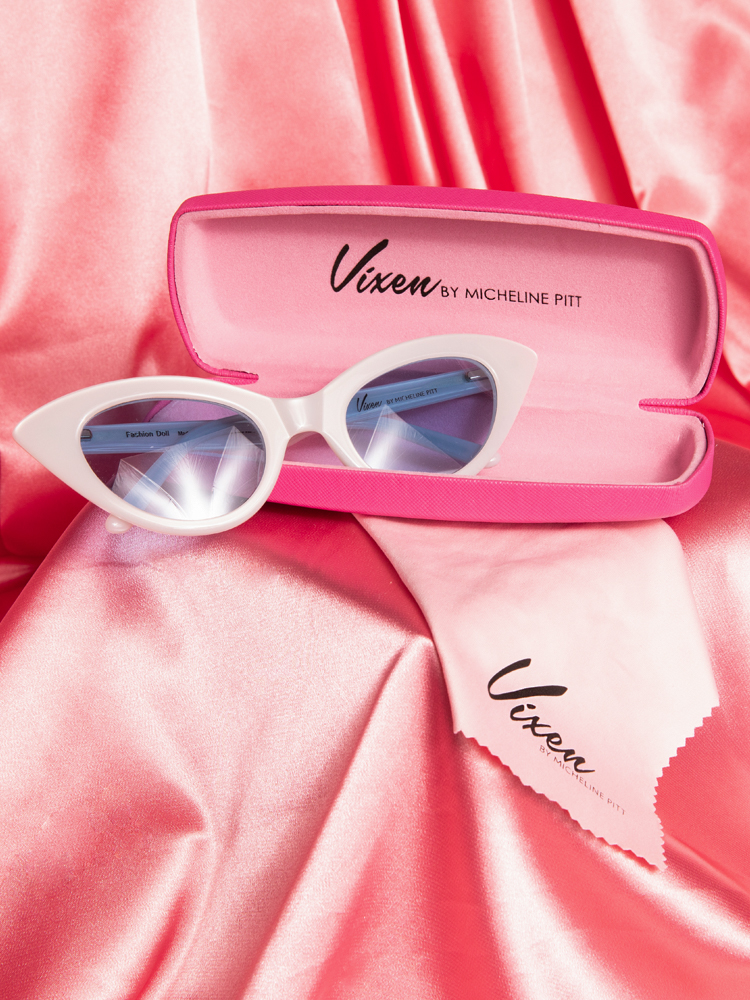 Stylized shot of the Fashion Doll Cat Eye Sunglasses in white placed on a pink satin background.