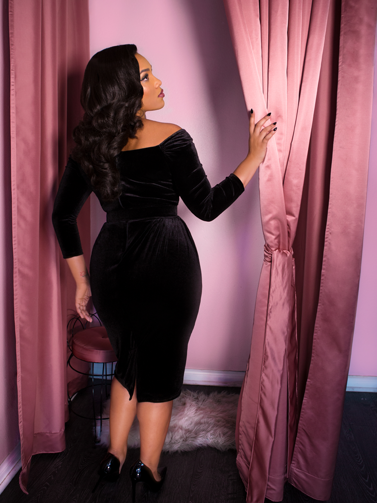 Back shot of model wearing a black Starlet Wiggle Cocktail style dress