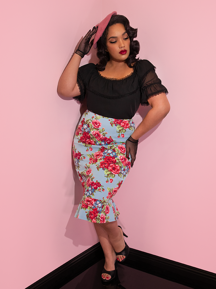 Ashleeta wearing black mesh gloves and a pink beret modeling the Vixen flutter skirt in blue and red rose print paired with a black peasant top.