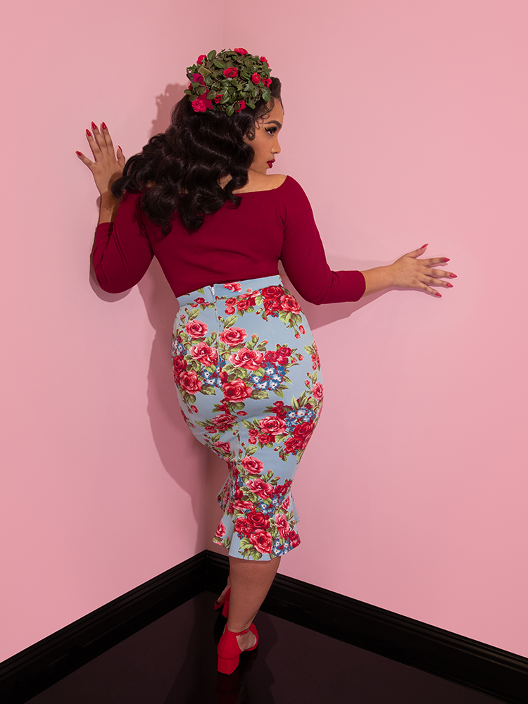 A back view of Ashleeta wearing a floral hat modeling the Vixen flutter skirt in blue and red rose print paired with a red tie up top.