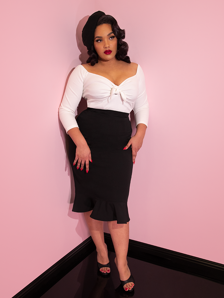 Ashleeta wearing a black beret modeling the Vixen flutter skirt in black paired with a white tie top.