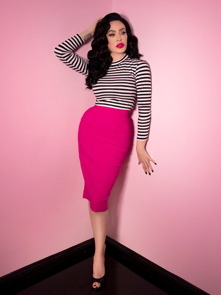 Full length shot of Micheline Pitt wearing a hot pink skirt along with the Girl Gang Crop Top in Black and White Stripe from Vixen Clothing.