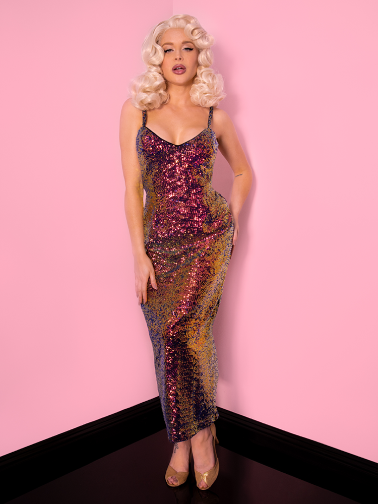 Looking directly at the camera, a vintage era model in a platinum blonde wig models a glamorous shiny sequin dress.