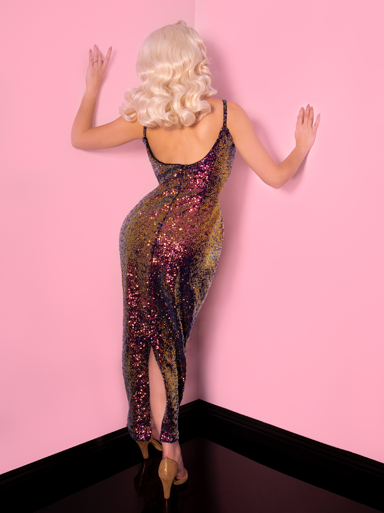 Back shot of model with platinum blonde wig wearing a scarab sequined dress while bracing herself against pink walls.