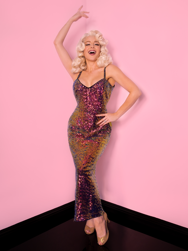 Posing model wearing a platinum blonde wig and a glitzy sequin dress.