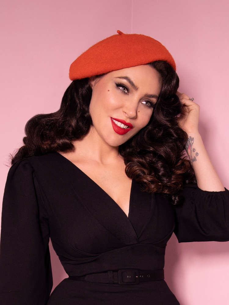 Smiling with her head turned to one side, Micheline Pitt models the a retro style beret in Halloween Orange color.