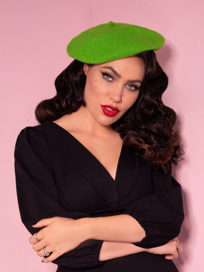 Micheline Pitt shot from the waist up wearing a green beret with a long sleeve top.