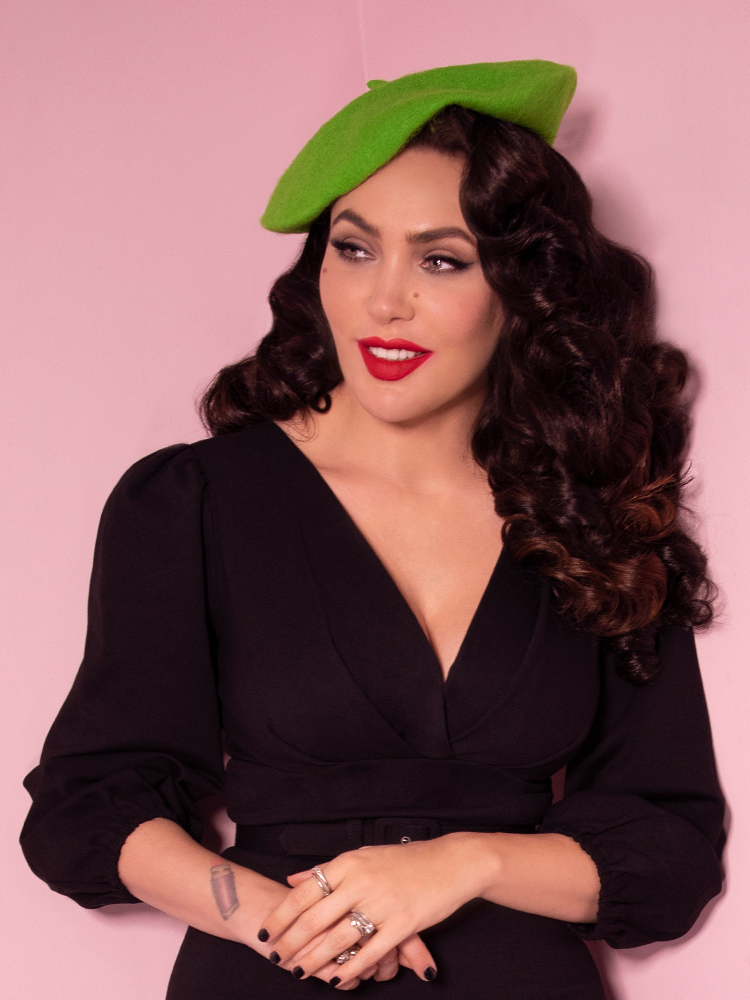 Smiling and looking off camera, Micheline Pitt wears the Halloween Slime Green Vintage Style Beret along with a vintage inspired long sleeve black top.