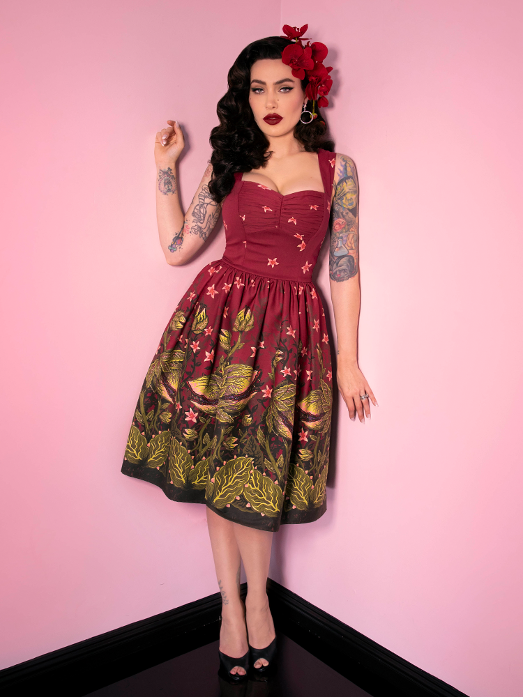 Micheline Pitt wearing a burgundy swing dress with a man-eating monster retro style print.