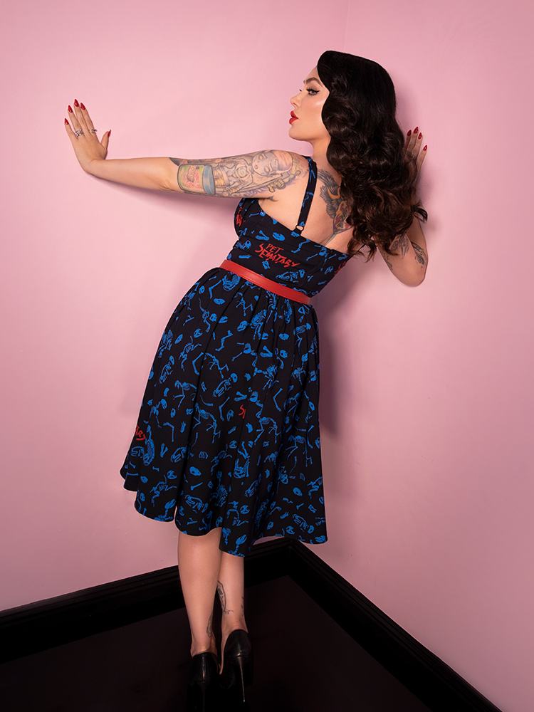 Back shot of Micheline Pitt wearing a black retro inspired dress with animal bone design adorned all over.
