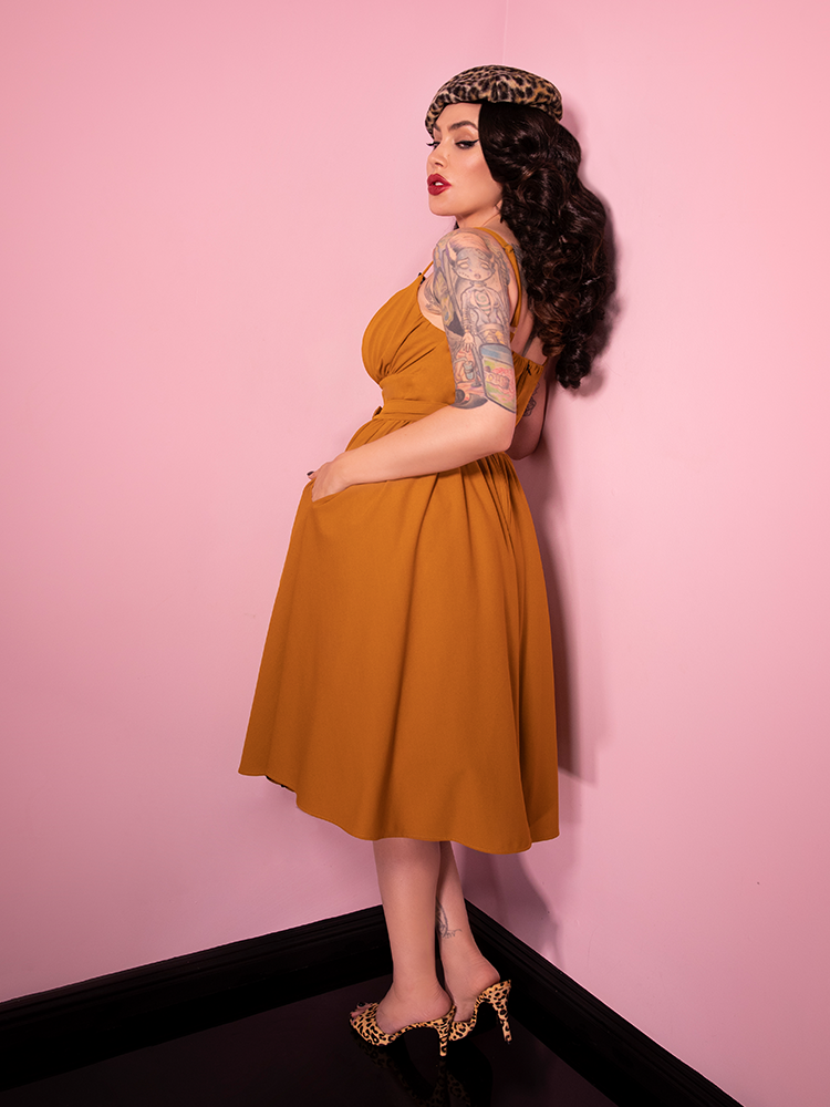With her body facing away from the camera and looking back alluringly at the camera, Micheline Pitt shows off the Ingenue Dress in Vintage Mustard Print.
