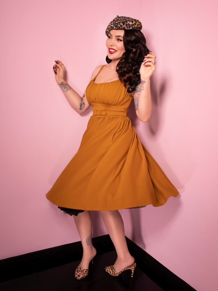 Micheline Pitt spins in the mustard print Ingenue Dress from vintage clothing retailer Vixen Clothing.