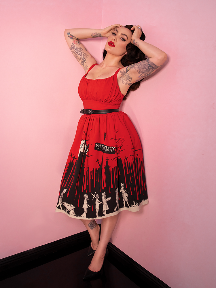 Micheline Pitt, posing against pink walls with black flooring, runs her fingers through her hair while wearing the Pet Sematary Ingenue Dress from Vixen Clothing - a vintage inspired clothing brand.