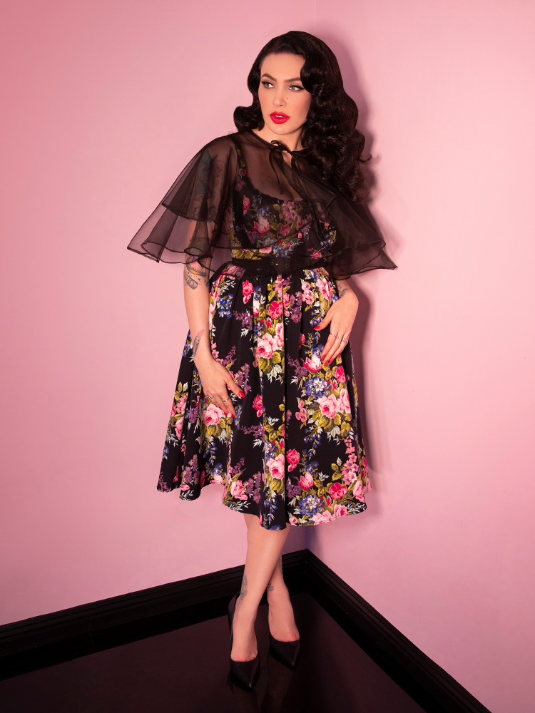 Micheline Pitt looking off to the side while wearing a retro style dress with floral print.