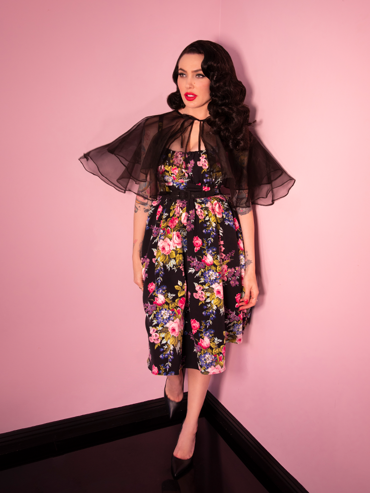 Model wearing a vintage style black capelet and black floral dress