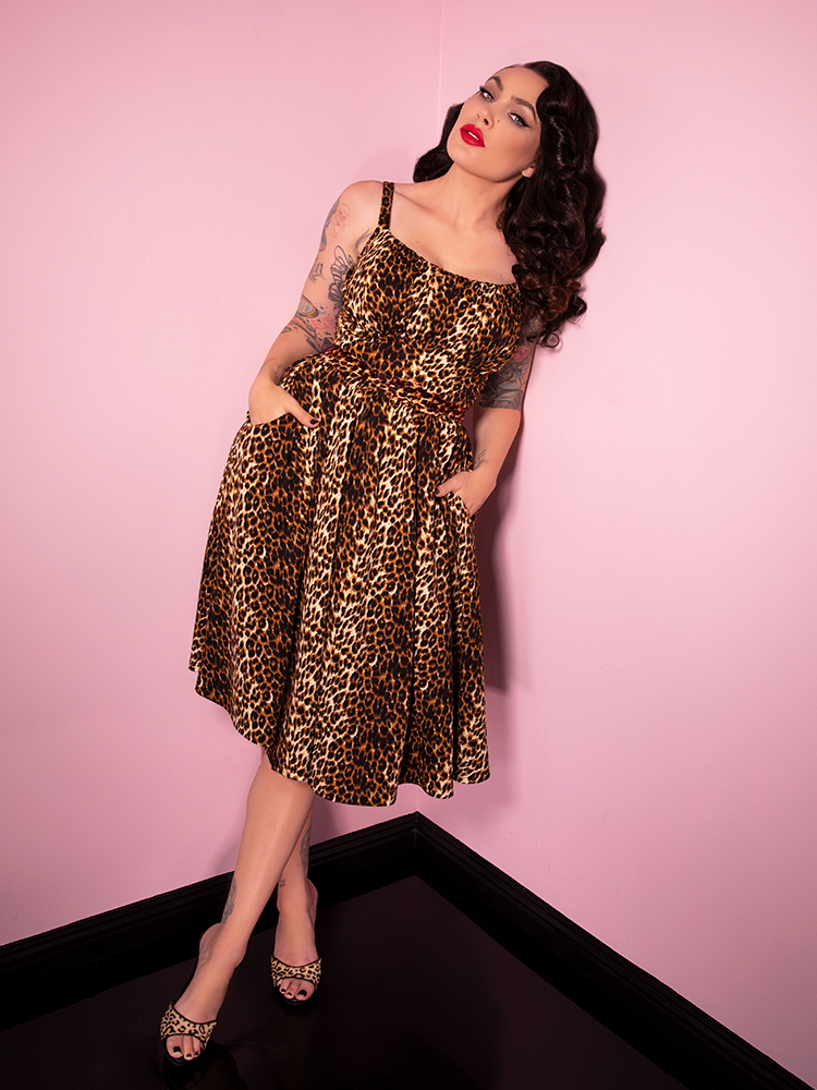 Posed with her hands in her pockets and leaning against a wall, Micheline Pitt looks gorgeous in the latest vintage inspired dress from Vixen Clothing.