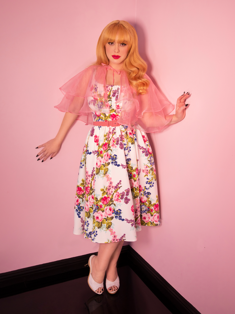 Model posing wearing a pink capelet and retro era floral vintage dress