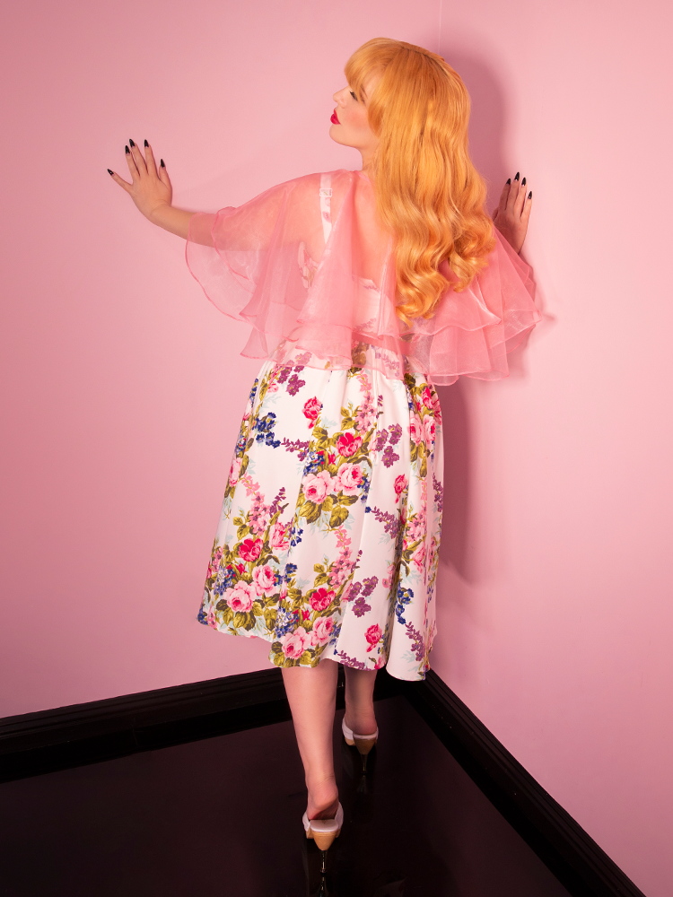 Model wearing a a white floral vintage dress and pink capelet