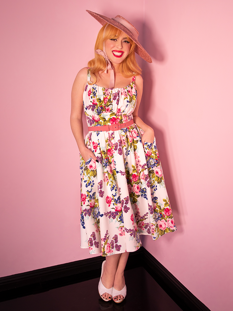 Model standing against a pink background wearing a white floral dress