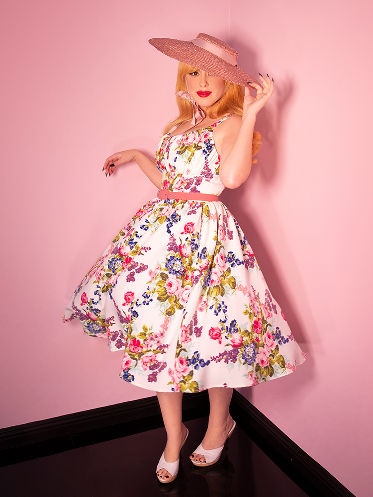 Model posing in a white retro style flora dress