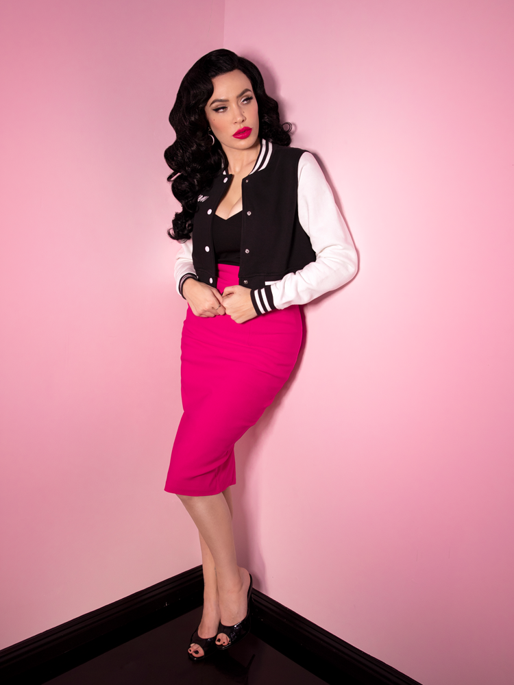 Full length shot of Micheline Pitt posing in the corner of her pink room, wearing a black and white letterman jacket, hot pink retro pencil skirt.