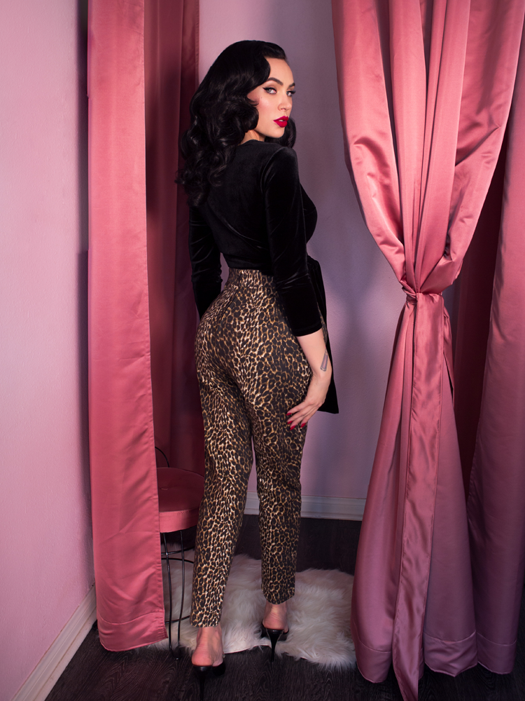 A stylized back shot of Micheline Pitt in a pink dressing room modeling the cigarette pants in leopard print paired with a black wrap top.