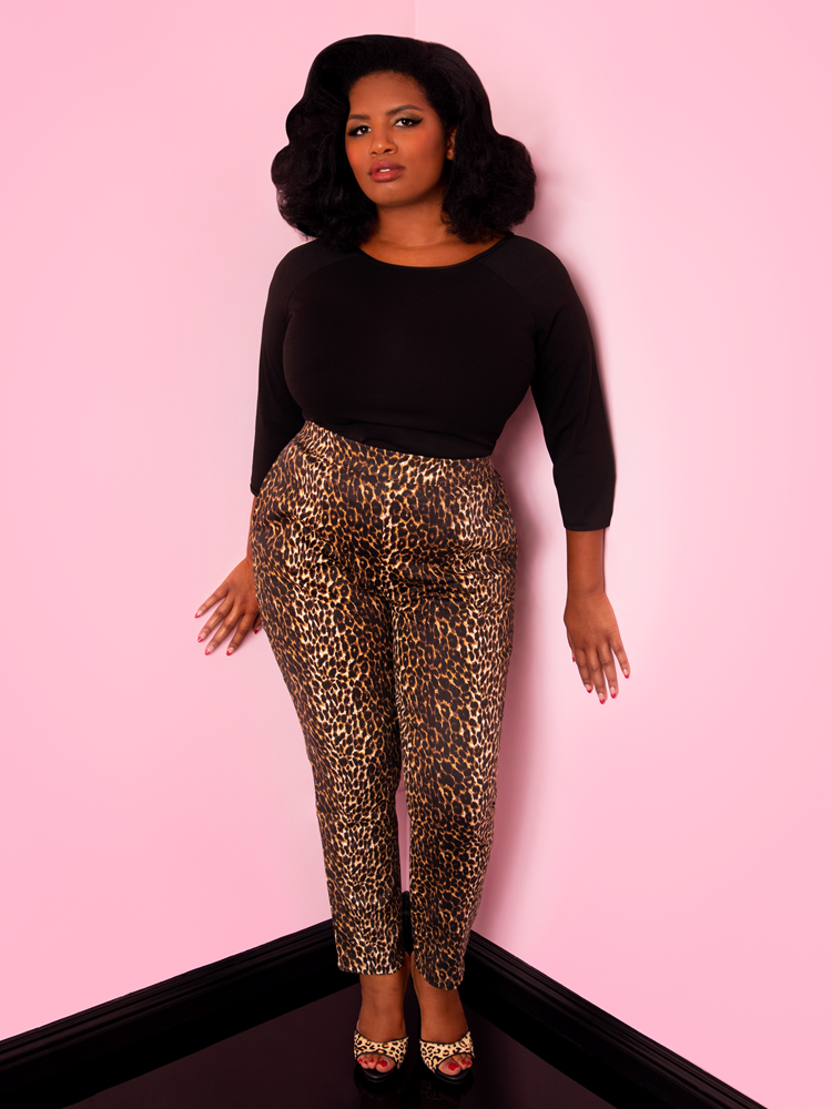 A full length shot of Aretina modeling the cigarette pants in leopard print by Vixen Clothing paired with a black top.