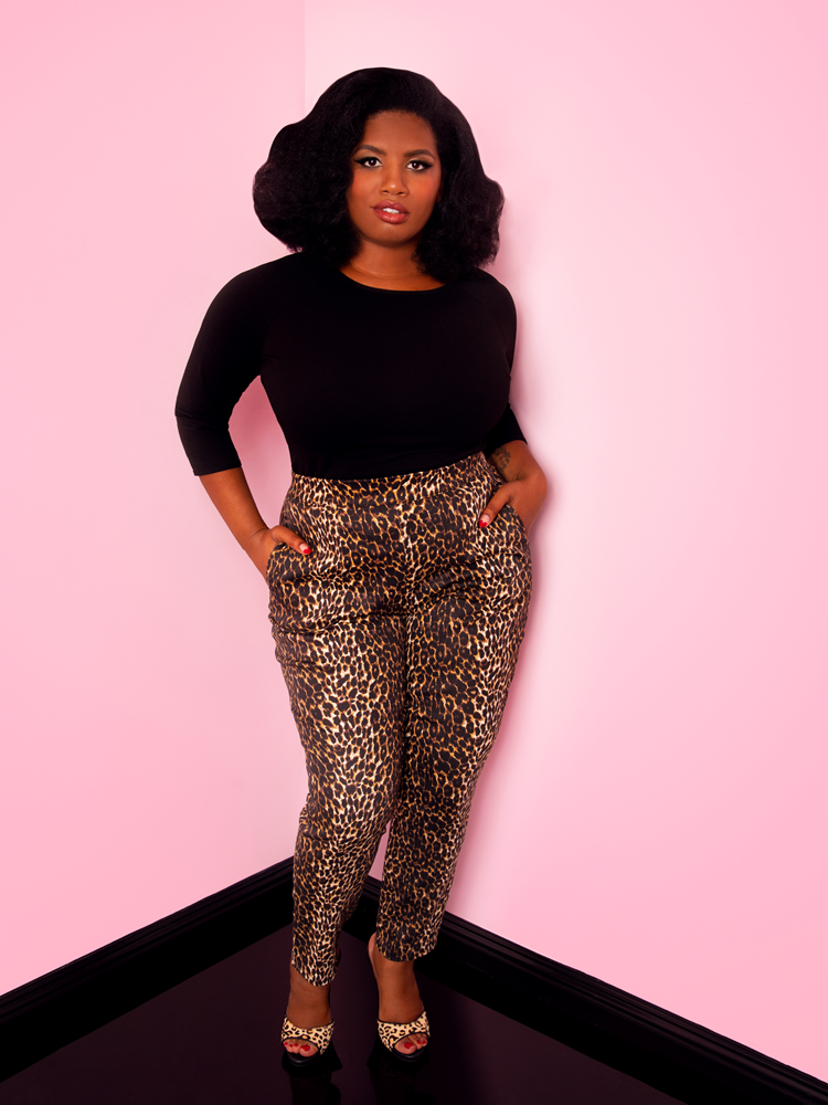 A full length shot of Aretina with her hands in her pockets modeling the cigarette pants in leopard print by Vixen Clothing paired with a black top.