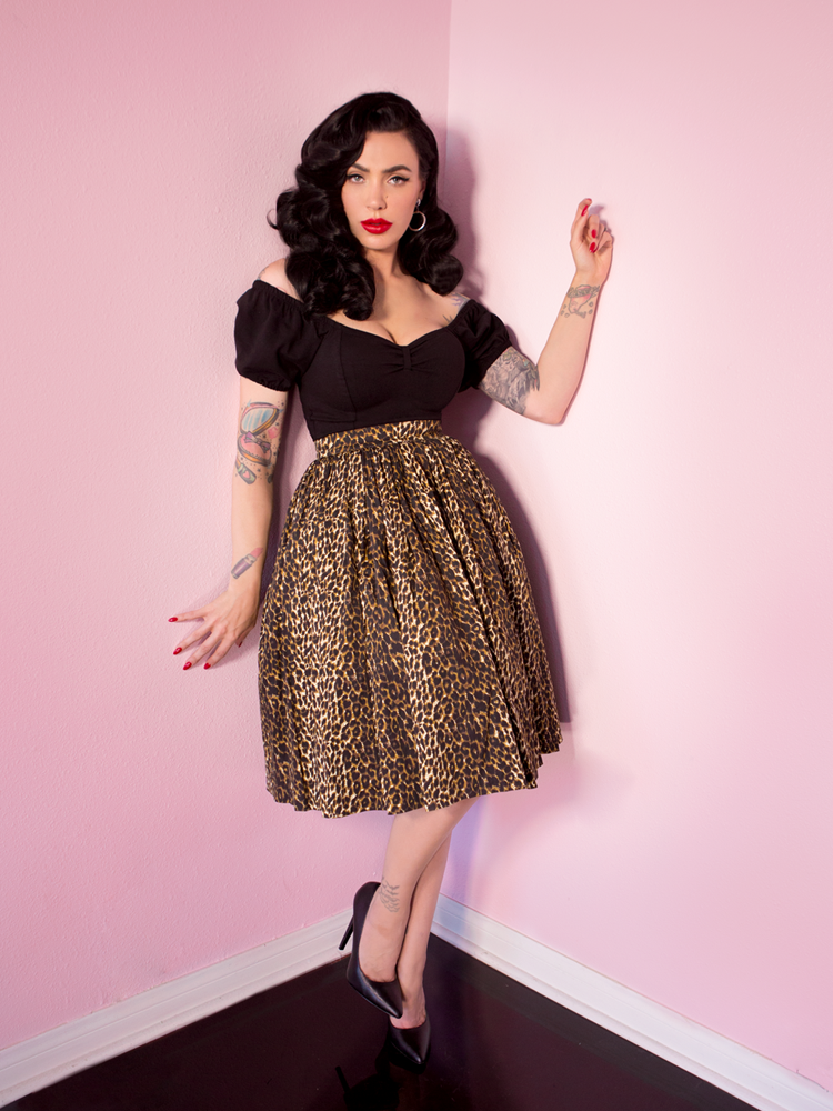 Striking a pose, Micheline Pitt is showing off her retro swing skirt in leopard print along with a black vintage style top.